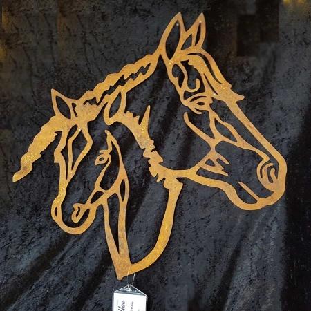 Pferd mit Fohlen aus rostigem Metall als Wandbild